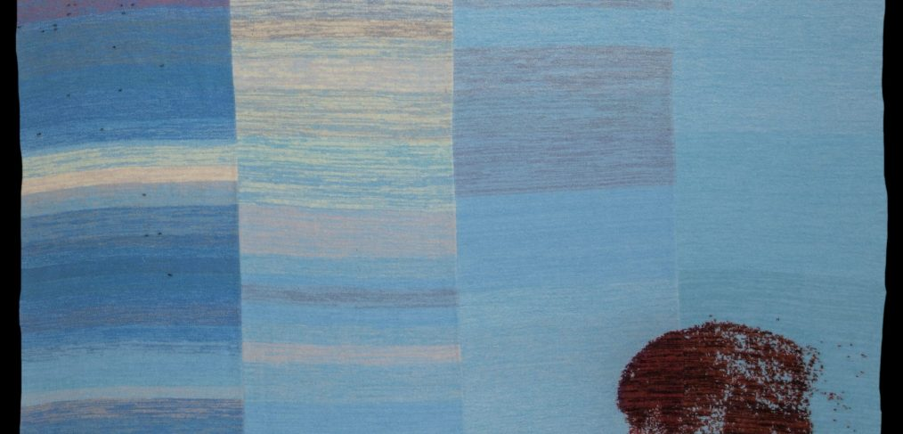 Kite rug in shades of blue with child looking over shoulder