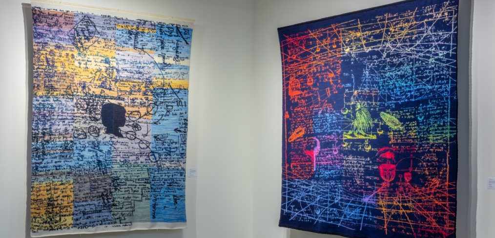 Photo of installation view of two large rugs from Lessons of Empathy in Wonderland exhibition at the Schweinfurth Memorial Art Center, Auburn, NY